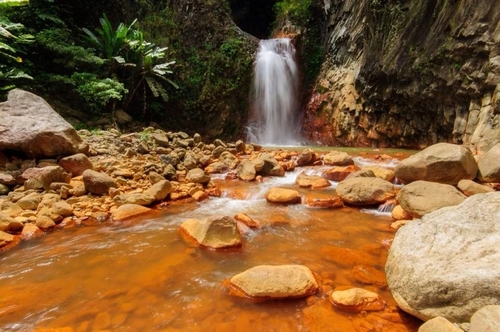 waterfall with red rocks surrounding the water