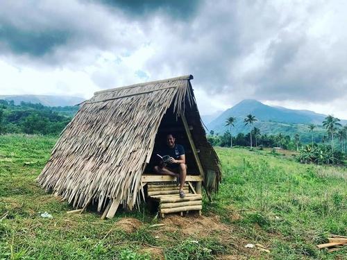 man reading inside a small hut at Editha Farm, Ozamiz