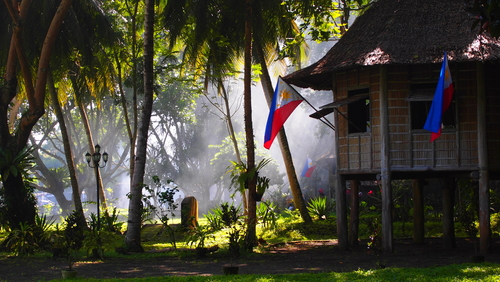 nipa house with philippine flages near the window  at Dapitan